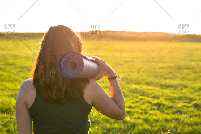 Woman carrying rolled up yoga mat on shoulder outside in grassy meadow