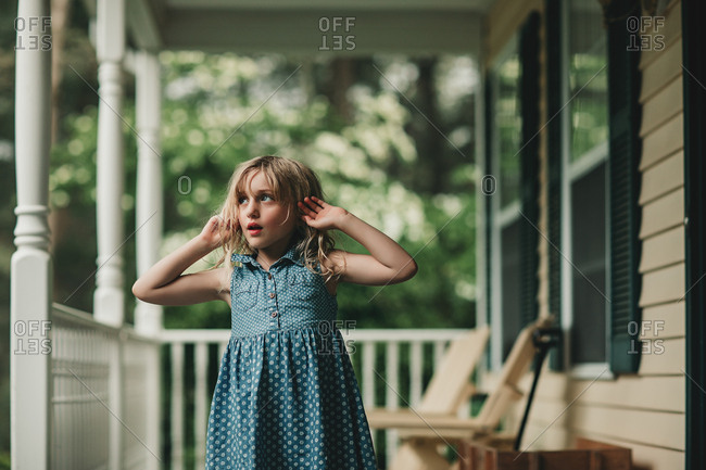 Girl staring off on summer porch