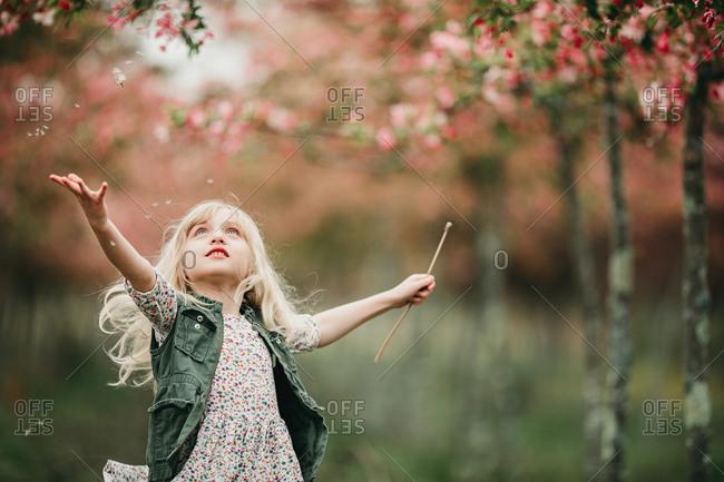 Girl tossing flower petals outside