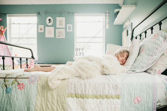 Girl on sunlit bed asleep