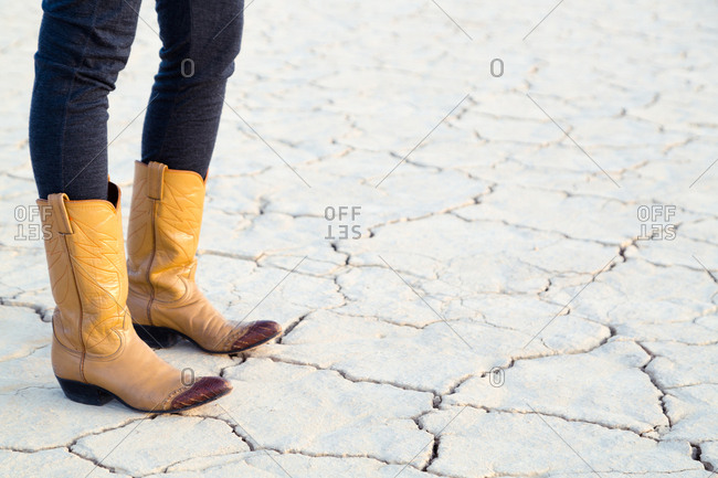 Person wearing cowboy boots standing on cracked ground in desert