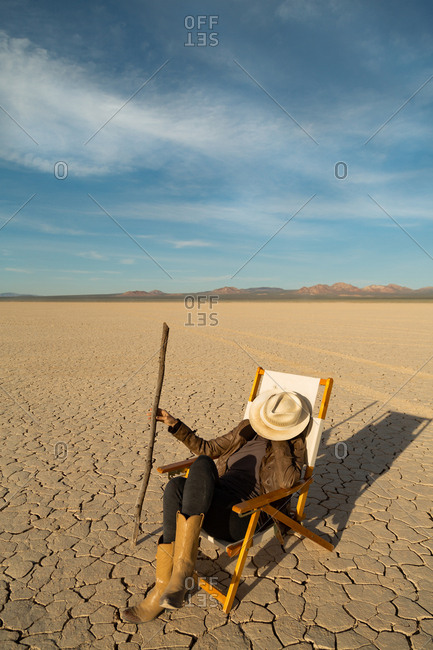 Person holding a walking stick while sitting in a folding chair in a vast dry lakebed in the desert