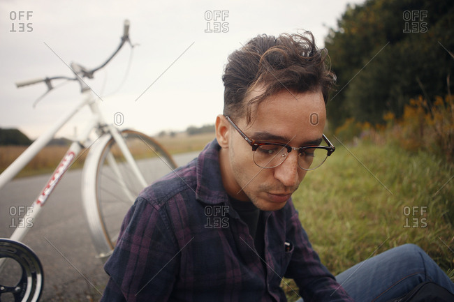Portrait of a man sitting on the ground next to bicycle