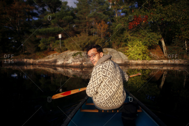 Man holding paddle seated in canoe looking over shoulder