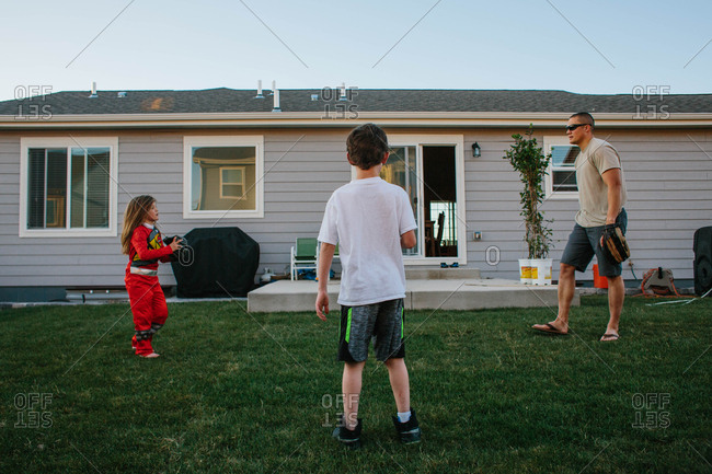 Boys with dad playing catch