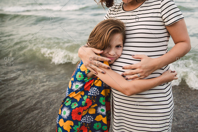 Girl hugging pregnant mom on beach
