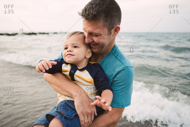 Happy dad with boy on beach