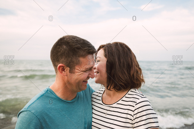 A couple smiling in beach embrace