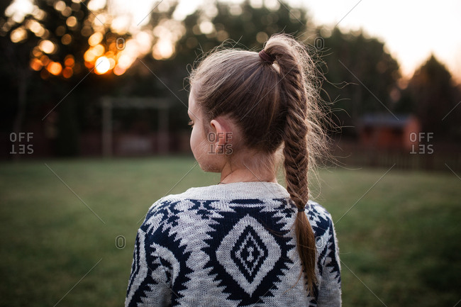 Girl with fishtail braid facing the sunset