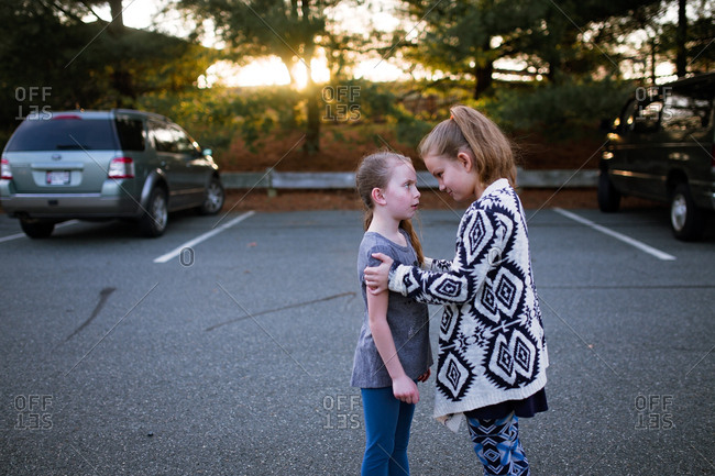 Two girls having a conversation in the parking lot