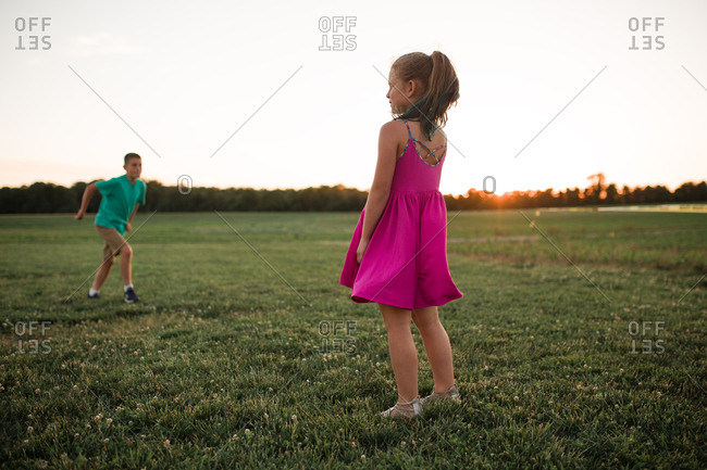 Girl in pink dress playing in the grassy field