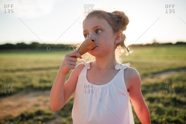 Girl eating an ice cream cone outside