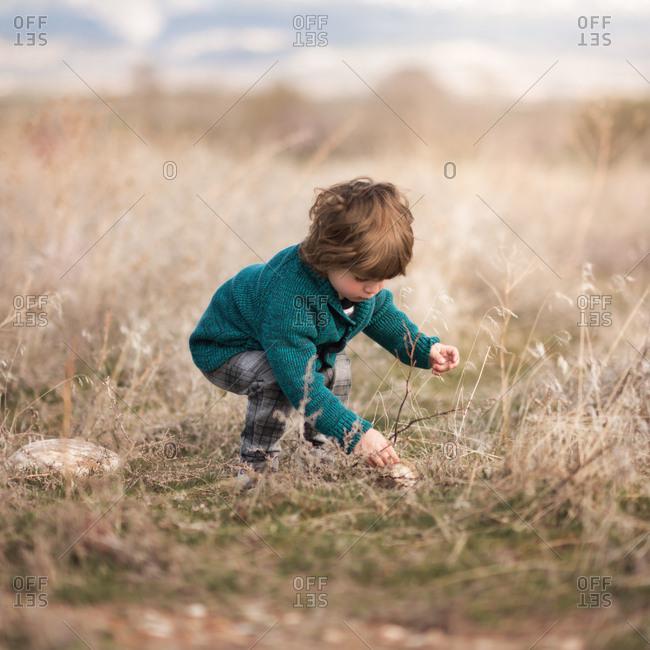 Toddler girl picking grass in field