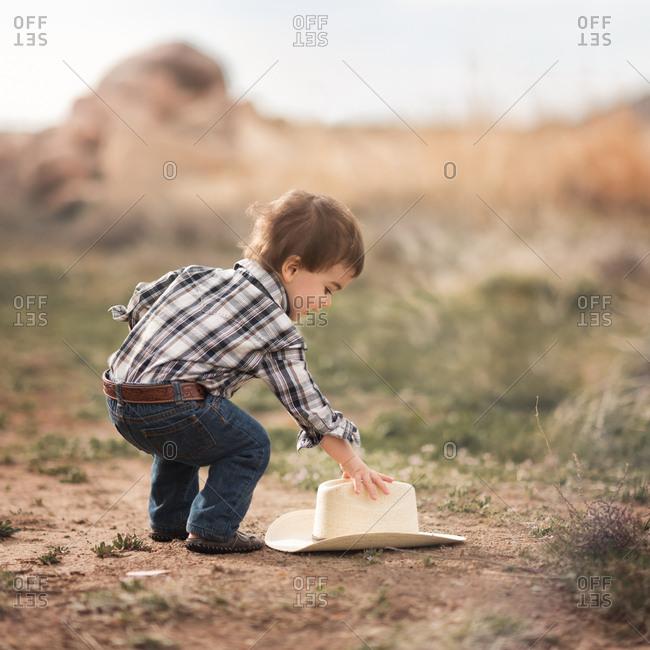 Toddler picking up cowboy hat
