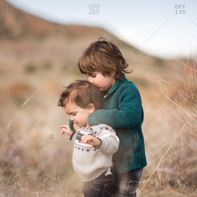 Toddlers hugging in rural field
