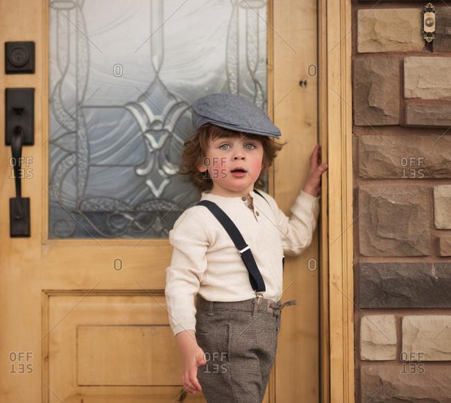 Boy in newsboy wear by door