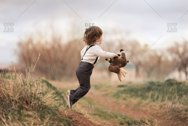 Boy in suspenders jumping from hill