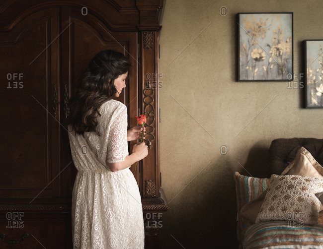 Woman holding rose in bedroom