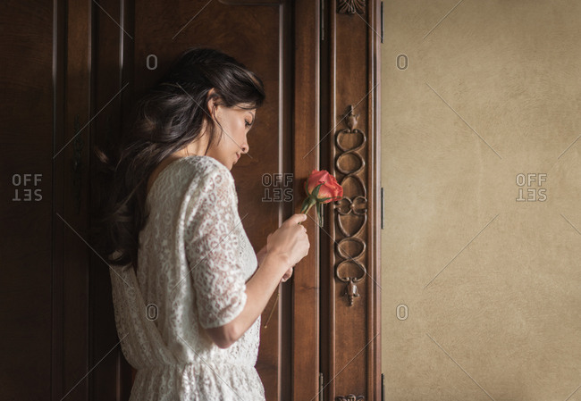 Woman holding rose by wardrobe
