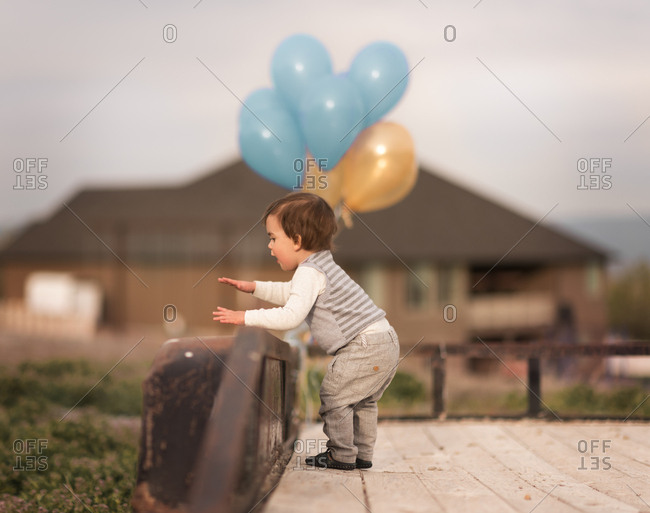 Excited toddler in yard near balloons