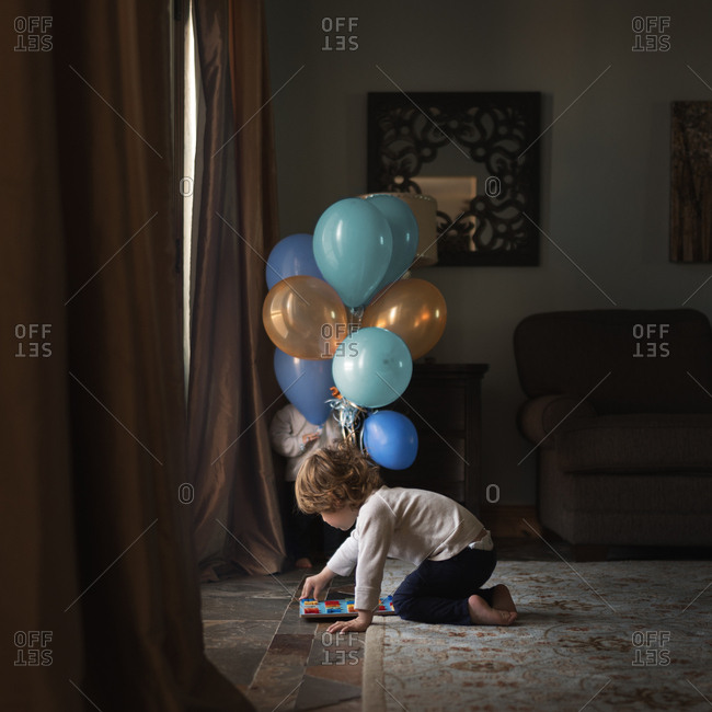 Toddler playing on floor near balloons