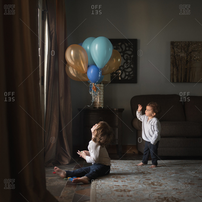 Toddlers in home near balloons
