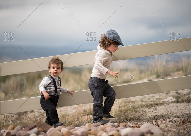 Boys in cute clothes by rural fence