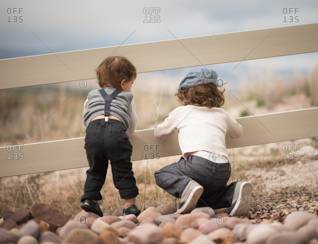 Two boys in trousers at rural fence