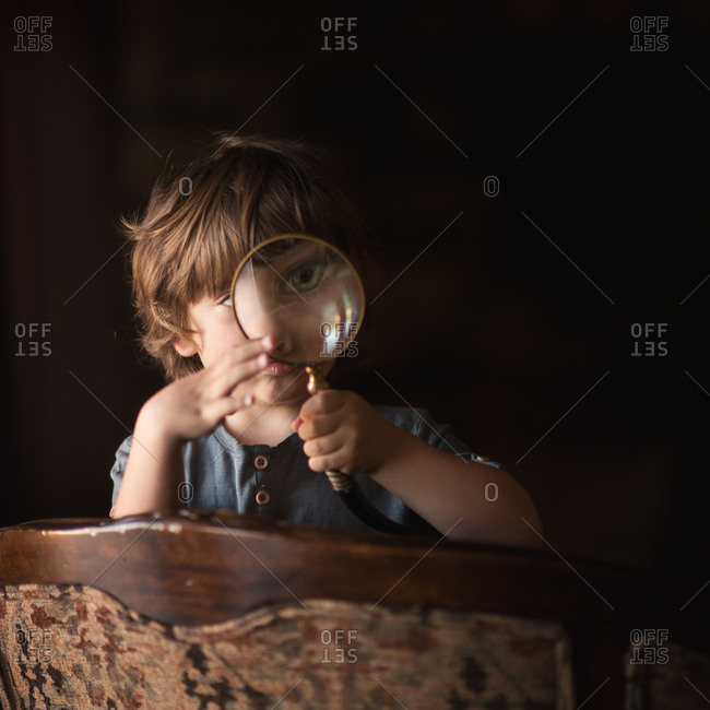 Boy at chair with magnifying glass