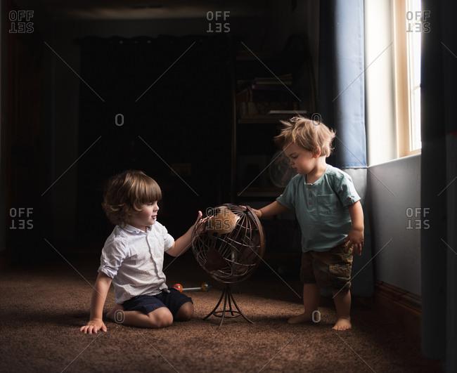 Toddler boys looking at old globe