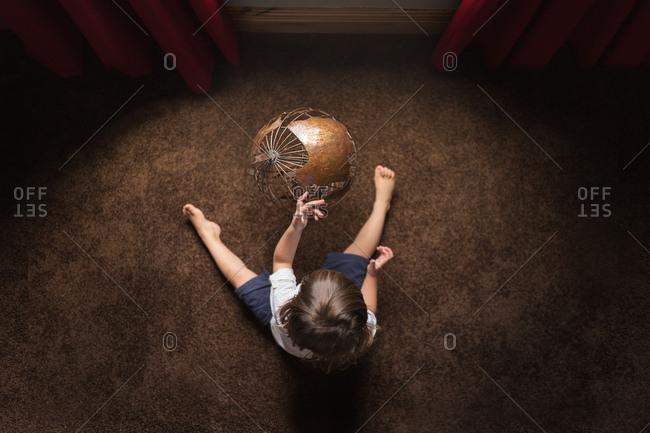 Toddler boy looking at old globe