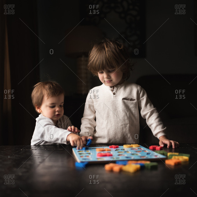 Boy watching toddler play with puzzle