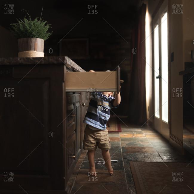 Toddler boy getting into kitchen drawer