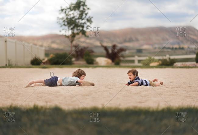 Toddler boys in sand pit in yard