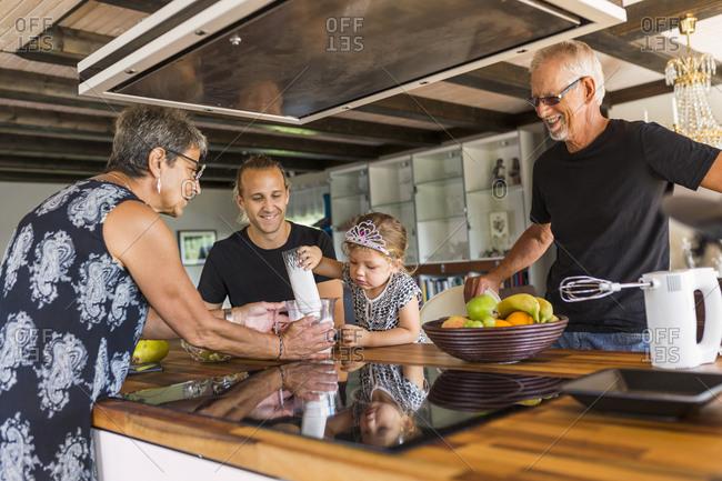 Grandparents preparing food with granddaughter