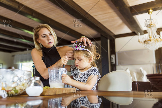 Mother putting tiara on daughter's head