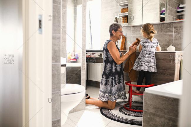 Grandmother and granddaughter brushing teeth in bathroom