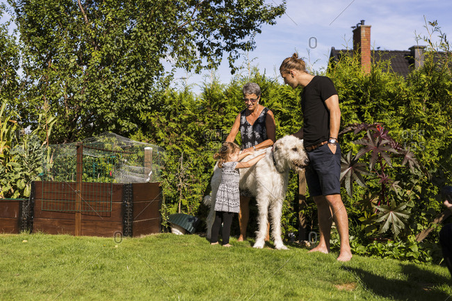 Grandmother and granddaughter stroking dog in garden