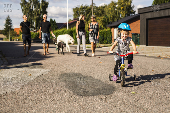 Girl riding bicycle, family in background