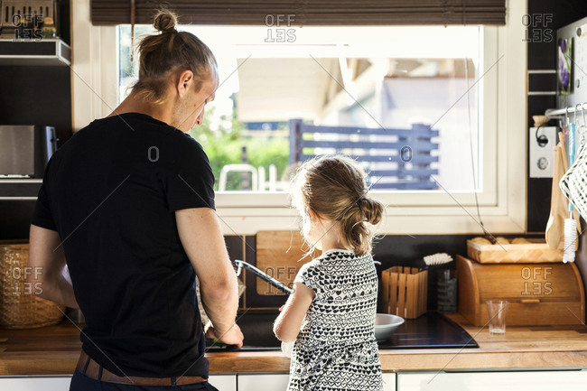 Father with daughter washing dishes