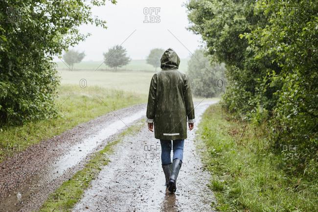 Rear view of woman in green raincoat walking in rain