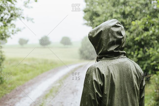Rear view of woman in green raincoat standing in rain