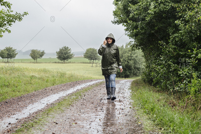 Woman walking up dirt road in rain