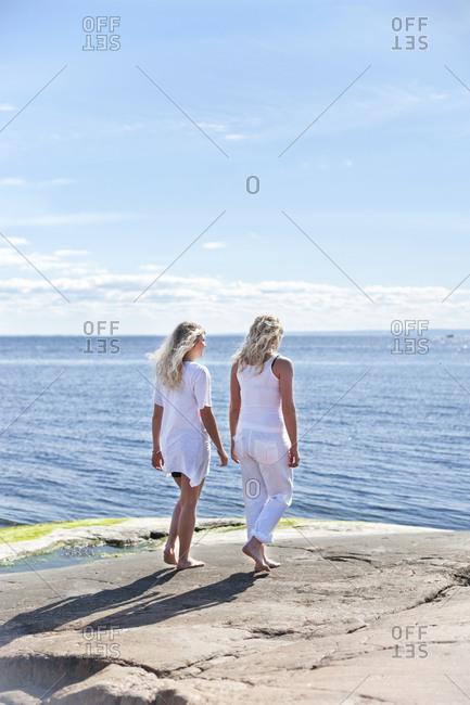 Women walking at sea - Offset