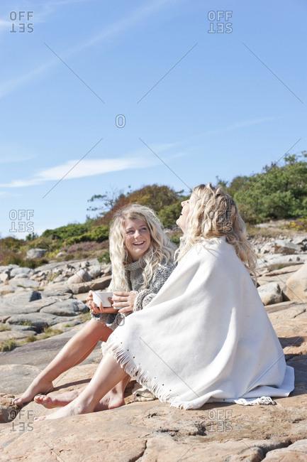 Happy women sitting on rocks