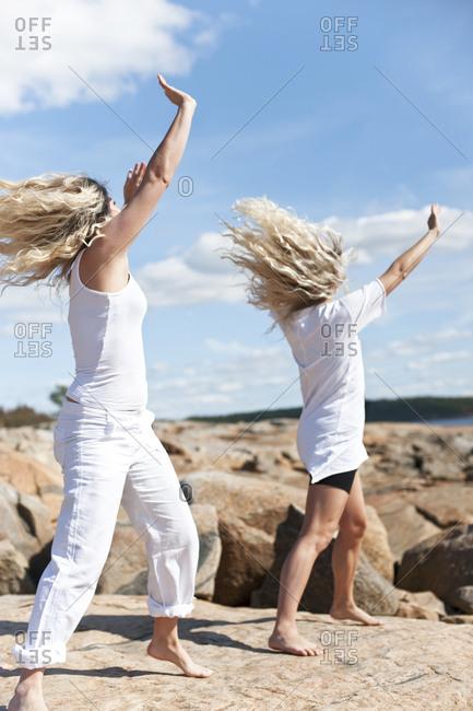 Women exercising on rocks - Offset
