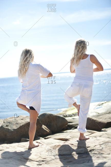 Women doing yoga at sea