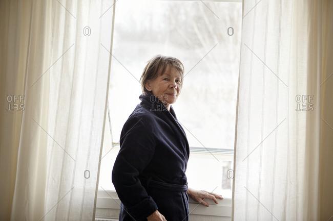 bd94c41add75ed Woman standing window Woman standing window