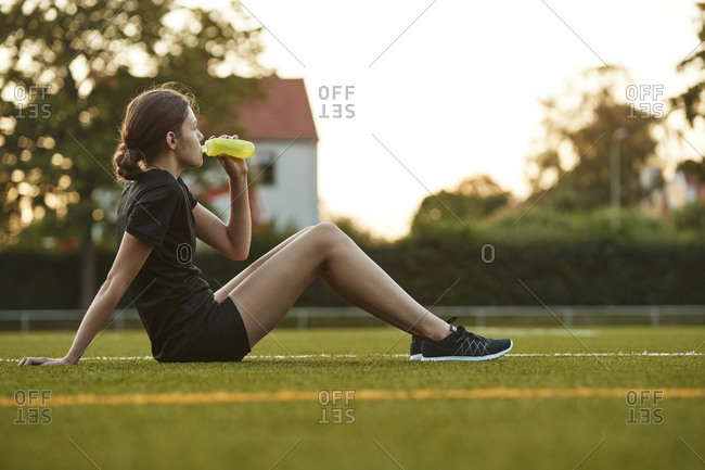 Teenage girl drinking from bottle in playing field