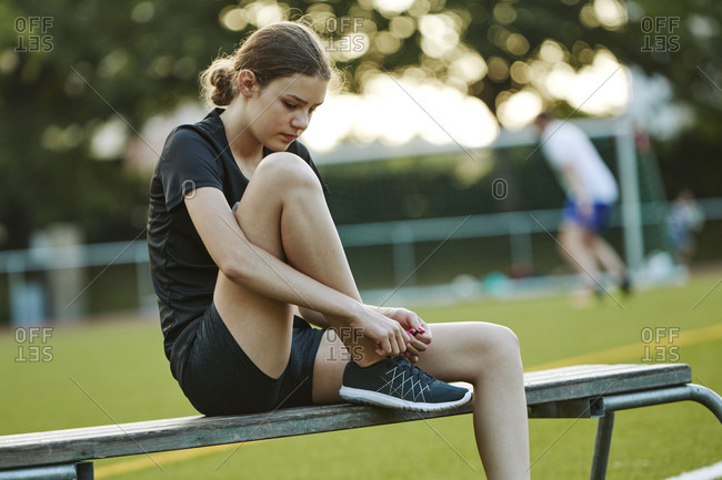Teenage girl tying shoelace while sitting on bench in playing field